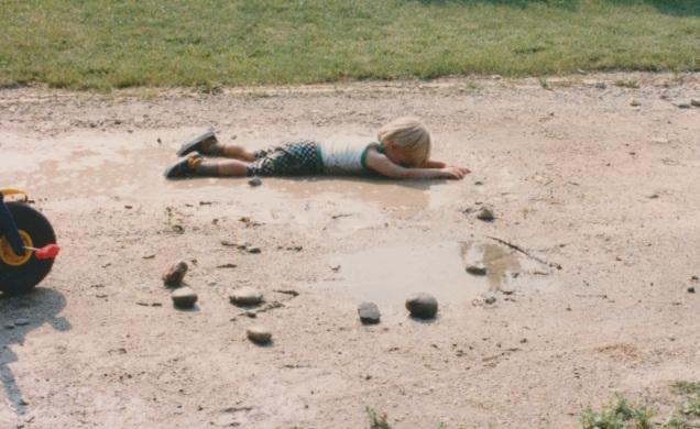 Child swims in mud.